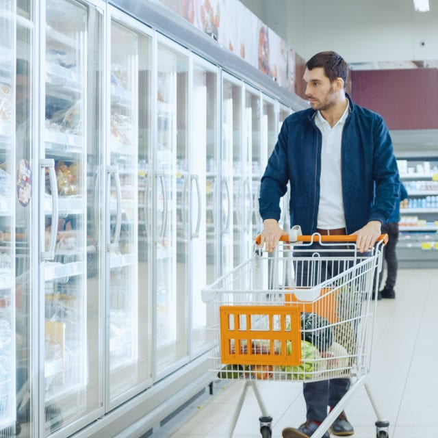 man in grocery store frozen food aisle